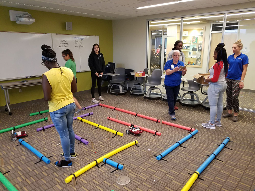 Female students navigating robots through a maze.